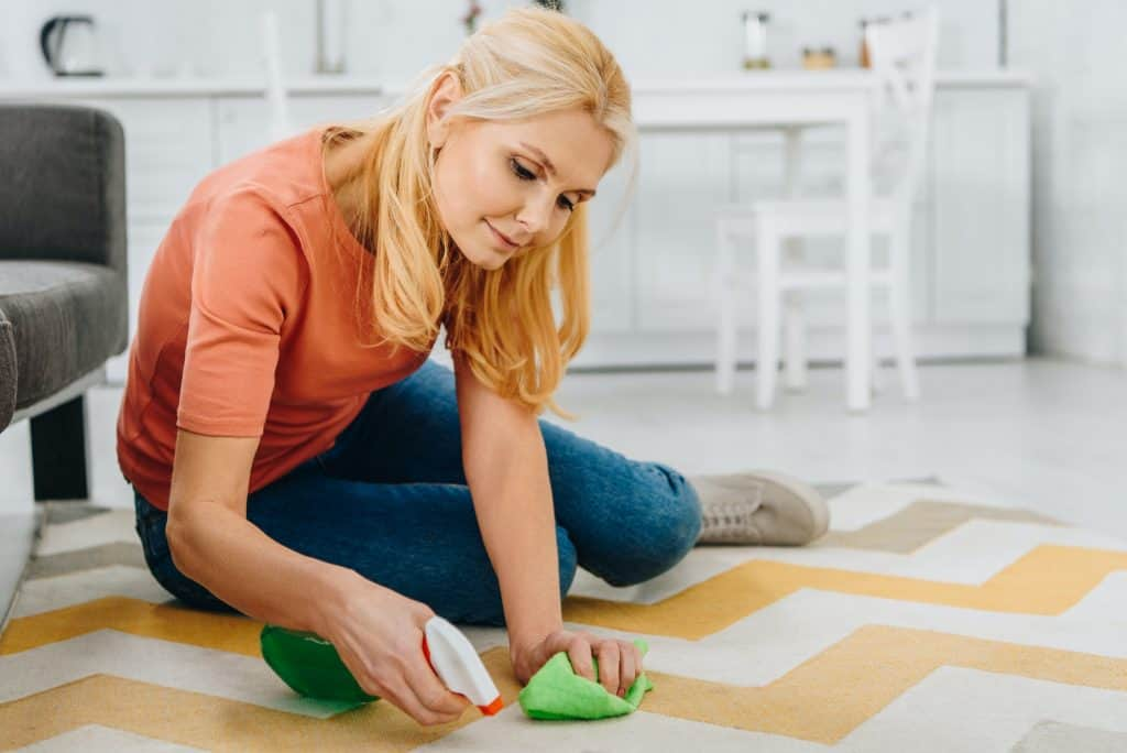 Concentrated blonde woman cleaning striped carpet with spray and rag